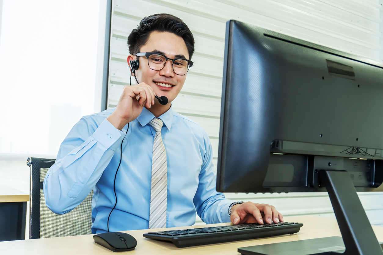 Call center, Service desk consultant talking on hands-free phone, Portrait of happy smiling male customer support phone operator at workplace, Call center business man talking on headset, Office and business concept